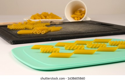 Various italian pasta on different colour cutboard
