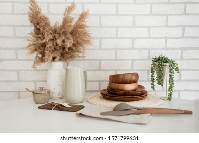 Various items on granite counter against white brick.
