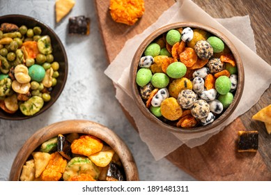 Various Japanese snacks in a wooden bowl close-up. Rice crackers with wasabi and nori, peanuts with sesame seeds, and other snacks. Mix traditional Japanese snack food. - Shutterstock ID 1891481311