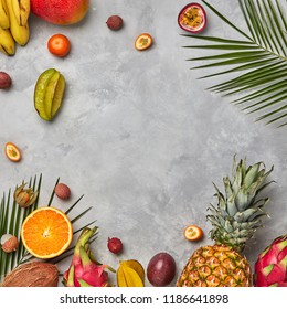 Various juicy exotic fruits, coconut, lychee, carom, pineapple and palm leaves on a gray concrete background with space for text. Food layout. Flat lay
