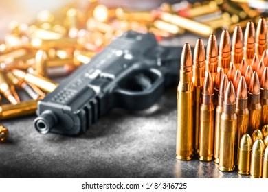 Various kind of bullets or ammonution on dark stone table. Bullet pile in war ammo background. Magazines, rounds and military technology. Banner or panorama guns photo.