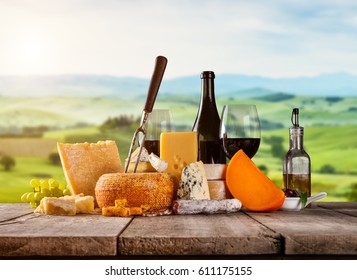 Various kind of cheese served on wooden table. Italian Toscana landscape on background. Traditional pieces of french and italy hand-made cheese. Copyspace for text