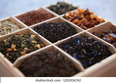 Various kind of dry tea - green, black, red, fruit and blue in wooden box on the table. Top view. Tea time concept.