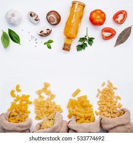 Various kind of Pasta Elbow Macaroni,Farfalle,Rigatoni,gnocco Sardo in hemp sack bags with ingredients sweet basil ,tomato ,garlic ,olive oil ,parsley ,bay leaves and champignon setup on white wooden.