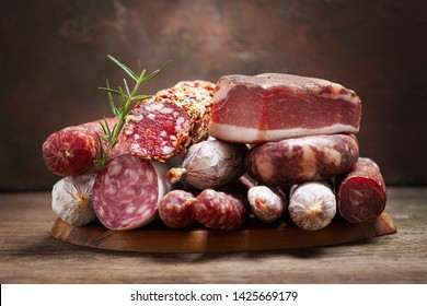 Various kind types of salami, speck and sausages on a wooden board