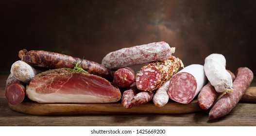 Various kind types of salami, speck and sausages on a wooden table