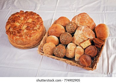 various kinds of bread  made from various flour in  a wicker basket next Slava cake