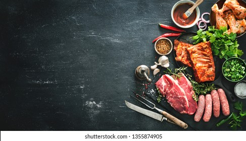 Various kinds of grill and bbq meats with vintage kitchen and butcher utensils. Chicken legs, steaks, sausages, pork ribs with herbs, spices, sauces and ingredients for grilling