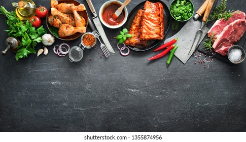 Various kinds of grill and bbq meats with vintage kitchen and butcher utensils. Chicken legs, steaks, pork ribs with herbs, spices, sauces and ingredients for grilling