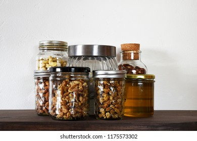 Various kinds of nuts and honey in glass jars