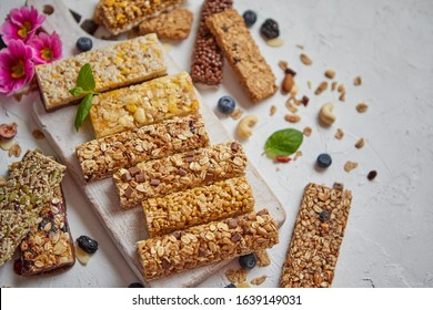 Various kinds of protein granola bars with dry fruits and berries. Placed on white wooden cutting board. Flat lay, top view.