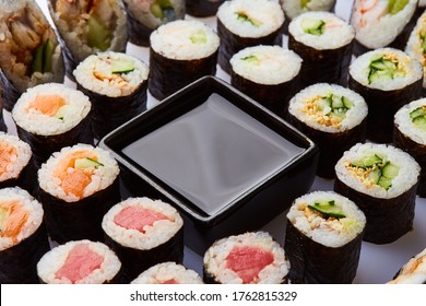 Various kinds of sushi roll set served on cutting board. Japanese food