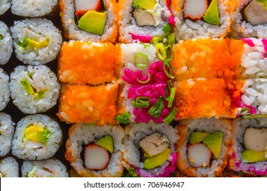 Various kinds of sushi rolls served. Dark background. Top view. Close up.