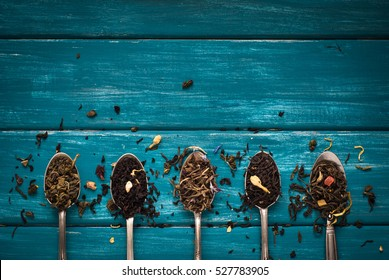 Various kinds of tea in spoons on blue wooden background. Dry Tea assortment.