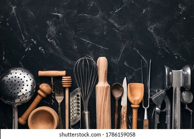 Various kitchen utensils and tools on a black stone background. Top view, flat lay, copy space. Collection kitchenware