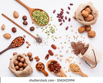 Various legumes and different kinds of nuts walnuts kernels ,hazelnuts, almond kernels,brown pinto ,soy beans ,flax seeds ,chia ,red kidney beans and pecan set up on white wooden table.