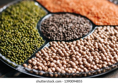 Various legumes red lentils, mung beans and chickpeas in a glass plate on a wooden table close up