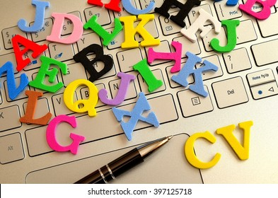 Various letters scattered with the inscription CV lying on a laptop
