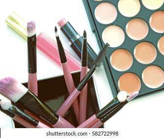 Various makeup brushes and beige palette on light background (Vintage tone)