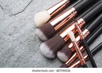 Various makeup brushes on black stone