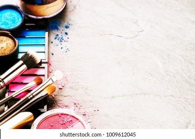 Verschiedene Schminkprodukte auf dunklem Hintergrund mit Kopienraum. Beauty- und Modekonzept