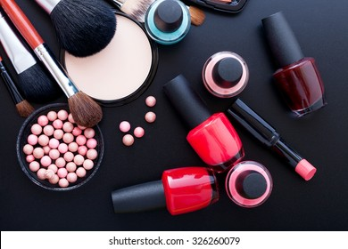 Various makeup products on dark background with copyspace. Cosmetics make up artist objects: lipstick, eye shadows, eyeliner, concealer, nail polish, powder, tools for make-up