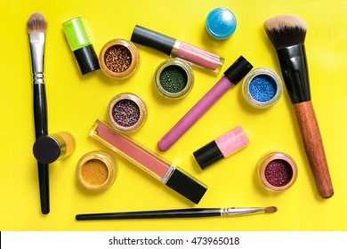 Various makeup products on yellow background