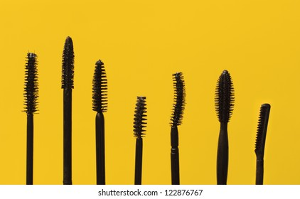 Various mascara wands, isolated on yellow background