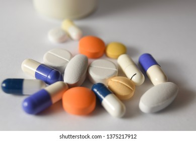 Various medical pills and capsules are split on a white background.
