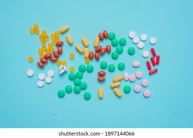 Various medical tablets on the blue flat lay background.