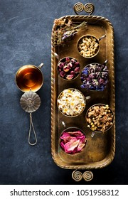 Various medicinal dried herbs and flowers in cups on a metal tray, and herbal tea, top view, flat lay