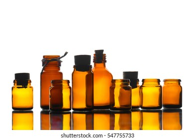 Various medicine yellow transparent bottles in the mirror table on the white background