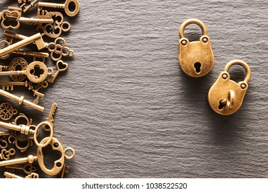 Various metal keys and locks over slate background