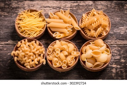Various mix of pasta on wooden rustic background, . Diet and food concept.