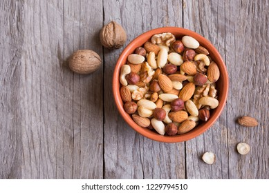 Various mixed nuts on wooden background
