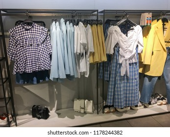 Various multi-coloured checkered clothes ,jacket ,blue jacket hanged in wardrobe In the store