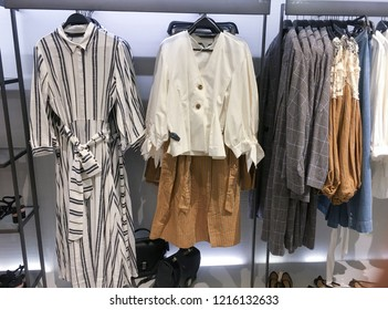 Various multi-coloured clothes ,sundress , jacket ,bag, shoes hanged in wardrobe In the store