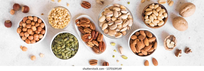 Various Nuts in  bowls on white background, top view, banner. Nuts assortment - pecans, hazelnuts, walnuts, pistachios, almonds, pine nuts, peanuts, pumpkin seeds.