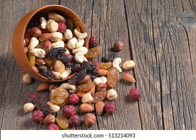 Various nuts and dried fruit in bowl and near on dark wooden table