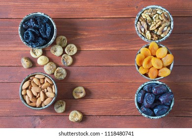 Various nuts and dried fruits (walnuts, almonds, prunes, dried apricots, date fruits, figs ) on  wooden background. Flat lay