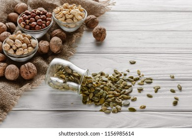 various nuts in glass bowls and pumpkin seeds in jar on white wooden surface