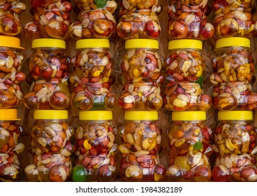 Various nuts in honey in funny bear shape jar. Stand with products: Cashews, walnuts, almonds, hazelnuts and other nuts in honey or syrup in jars. Selective focus.