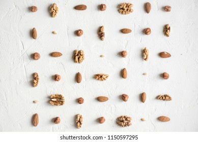 Various nuts (walnuts, hazelnuts, almonds and pine nuts) repetition on white background as pattern, flat lay with copy space.