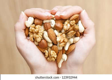 Various nuts in woman hands  forming heart shape
