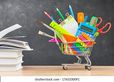 Various office supplies for school in a cart and textbooks on a wooden table on a blackboard background. The concept of preparing for school, the beginning of a new school year.