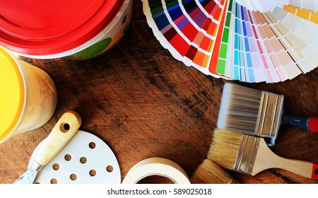 various painting tools and color palette on wooden background