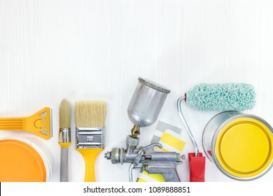 various painting tools on white wooden background. paint brush, roller, sprayer, yellow and orange paints cans, color samples. flat lay