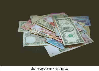 Various paper money on a black background