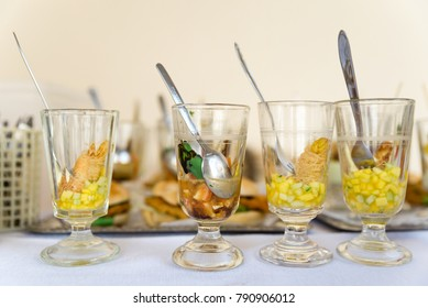 Various party snacks in glasses on a buffet