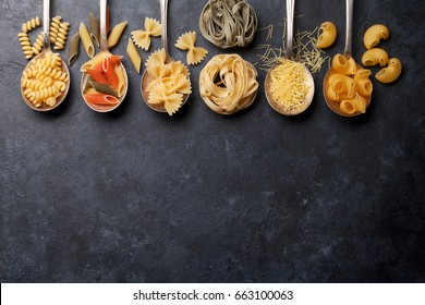 Various pasta on spoons over stone background. Top view with copy space